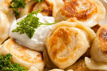Homemade Polish Pierogis with Sour Cream and Parsley photo