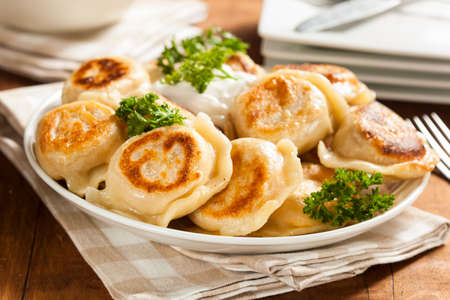 Homemade Polish Pierogis with Sour Cream and Parsley Stock Photo