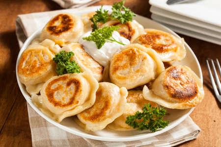 pierogi: Homemade Polish Pierogis with Sour Cream and Parsley Stock Photo