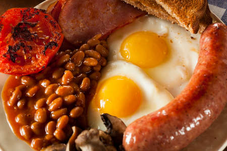 Traditional Full English Breakfast with Eggs, Bacon, Sausage, and Baked Beans photo