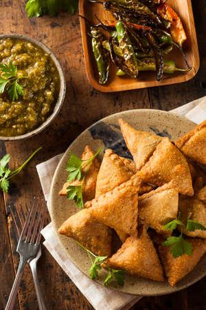 Homemade Fried Indian Samosas with Mint Chutney Sauce photo