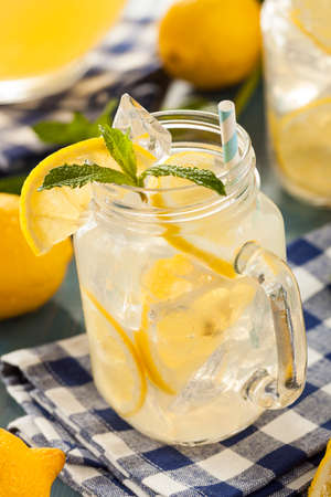 Homemade Refreshing Yellow Lemonade with Ice and Mint photo