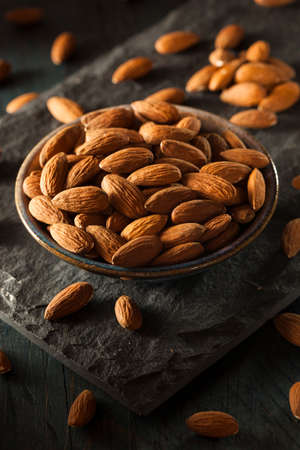Raw Organic Brown Almonds in a Bowl Stock Photo