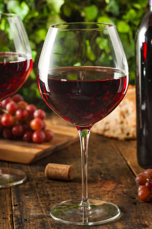 Refreshing Red Wine In a Glass with Grapes Stok Fotoğraf