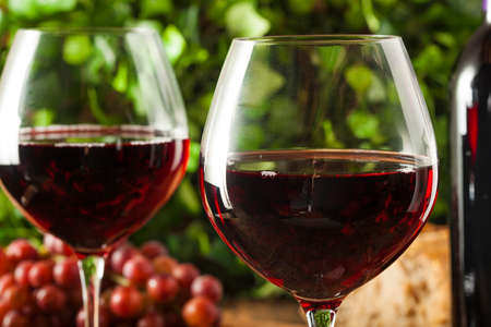 red wine pouring: Refreshing Red Wine In a Glass with Grapes Stock Photo