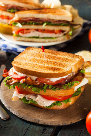 Turkey and Bacon Club Sandwich with Lettuce and Tomato photo