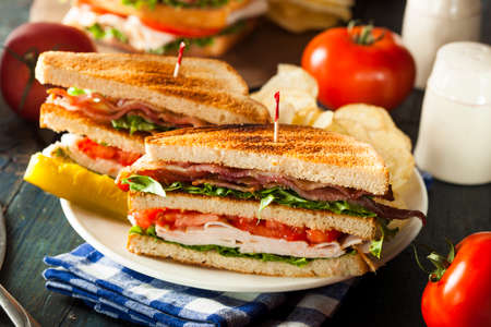 Turkey and Bacon Club Sandwich with Lettuce and Tomato Imagens