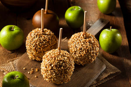 taffy: Homemade Taffy Apples with Peanuts on a Stick Stock Photo