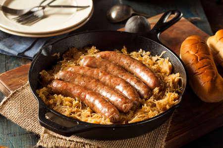 comida alemana: Asado Beer Bratwurst con saurkraut en una cacerola