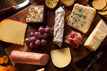 cheddar cheese: Fancy Meat and Cheeseboard with Fruit as an Appetizer Stock Photo