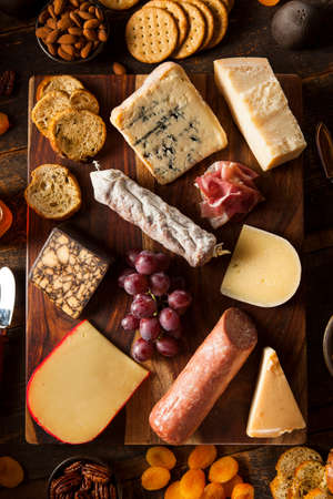 cheeseboard: Fancy Meat and Cheeseboard with Fruit as an Appetizer Stock Photo