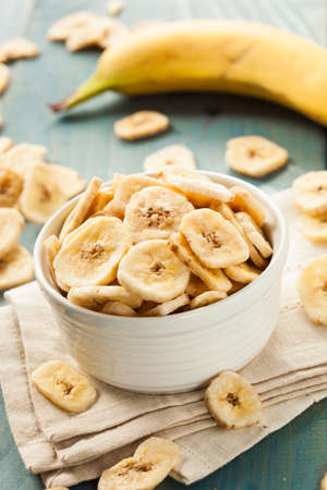 banana: Homemade Dehydrated Banana Chips in a Bowl Stock Photo