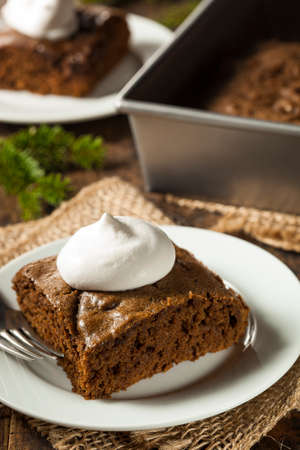 Homemade Brown Gingerbread Cake with Whipped Cream Imagens