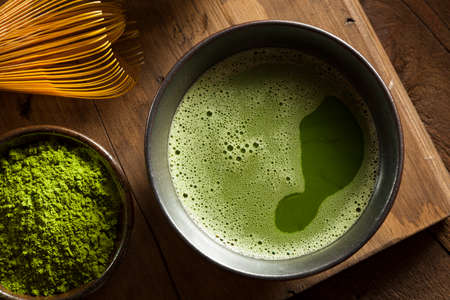 green background: Organic Green Matcha Tea in a Bowl