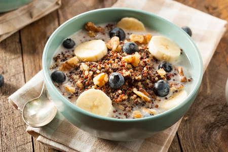 comiendo cereal: Orgánica desayuno quinua con leche y nueces Bayas