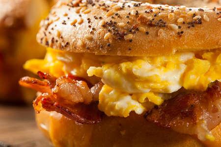 huevos revueltos: Sandwich abundante desayuno en un panecillo con tocino, huevo y queso