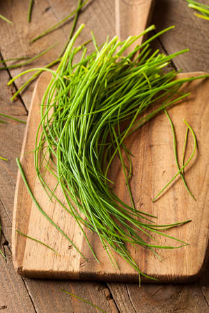 Raw Organic Green Chives on a Cutting Board