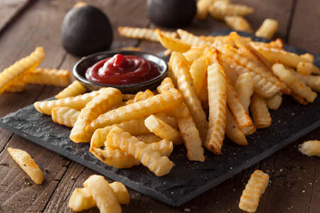 potato fries: Unhealthy Baked Crinkle French Fries with Ketchup Stock Photo