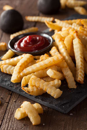 crinkle: Unhealthy Baked Crinkle French Fries with Ketchup Stock Photo