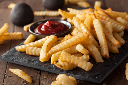 Unhealthy Baked Crinkle French Fries with Ketchup Imagens