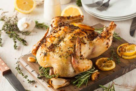 pollos asados: Hecho en casa de limón y hierbas Pollo entero en una tabla de cortar