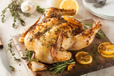 pollo rostizado: Hecho en casa de limón y hierbas Pollo entero en una tabla de cortar