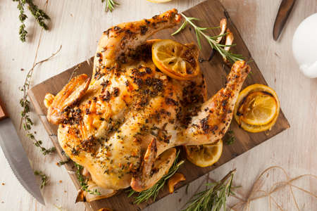 baked chicken: Homemade Lemon and Herb Whole Chicken on a Cutting Board