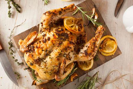 Zelfgemaakte citroen en Herb hele kip op een snijplank Stockfoto