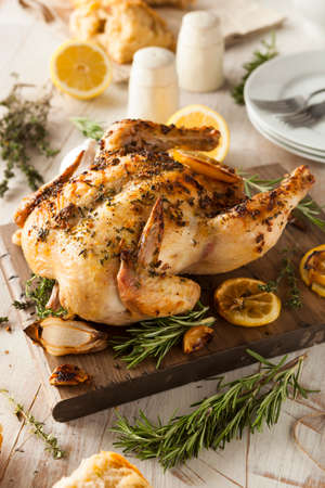 baked meat: Homemade Lemon and Herb Whole Chicken on a Cutting Board