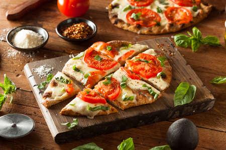 Zelfgemaakte Margarita Flatbread Pizza met tomaat en basilicum Stockfoto