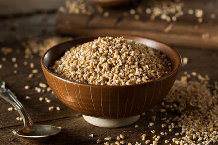 to cut: Raw Organic Steel Cut Oats in a Bowl Stock Photo