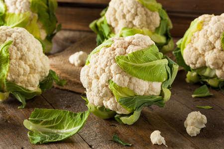 head of cauliflower: Raw Organic Cauliflower Heads with Fresh Green Leaves