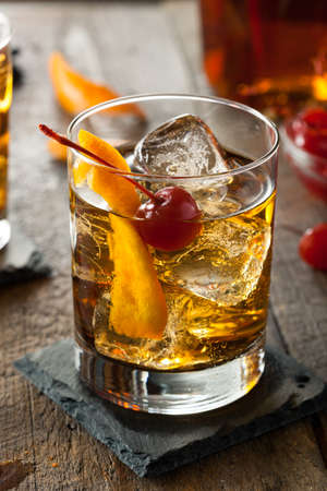 tomando alcohol: Homemade Cocktail pasada de moda con las cerezas y c�scara de naranja Foto de archivo