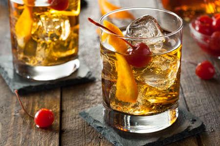 cocteles: Homemade Cocktail pasada de moda con las cerezas y c�scara de naranja Foto de archivo