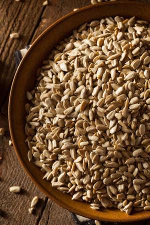 semillas de girasol: Organic Raw cascado semillas de girasol en un taz�n de fuente Foto de archivo