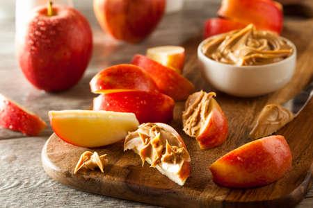 Las manzanas orgánicas y la mantequilla de cacahuete para picar Foto de archivo