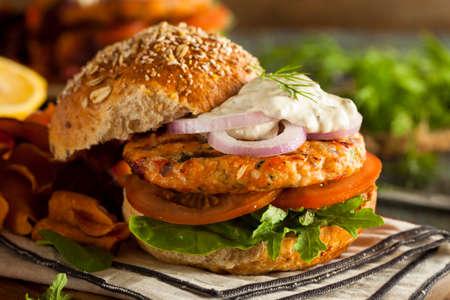 comidas rapidas: Hecho en casa hamburguesa de salm�n org�nico con salsa t�rtara Foto de archivo