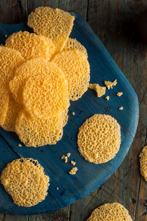 crisps: Homemade Parmesan Cheese Crisps on a Cutting Board Stock Photo