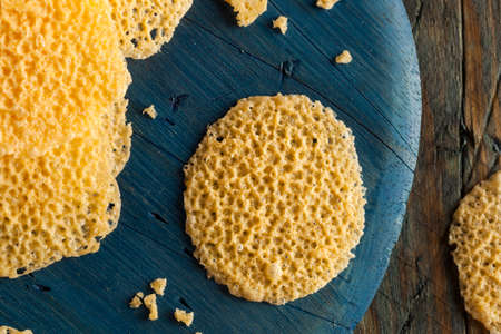 browned: Homemade Parmesan Cheese Crisps on a Cutting Board Stock Photo
