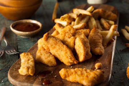 Homemade Breaded Chicken Tenders with Fries and BBQ Sauce Foto de archivo