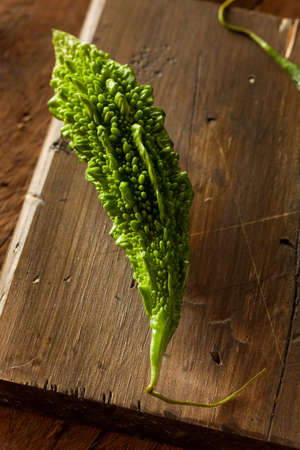 bitter melon: Raw Green Organic Bitter Melon on a Cutting Board