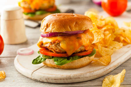 burger: Homemade Healthy Chicken Burger with Cheese Lettuce and Tomato Stock Photo