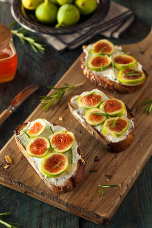 cream cheese: Homemade Fig and Goat Cheese Toast with Rosemary and Honey Stock Photo