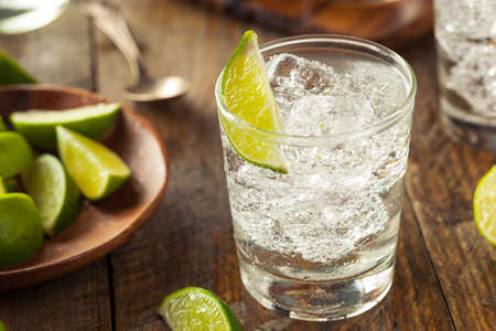 drinking soda: Alcoholic Gin and Tonic with a Lime Garnish