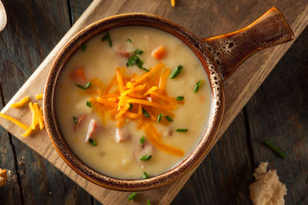 Homemade Beer Cheese Soup with Chives and Bread Stock Photo