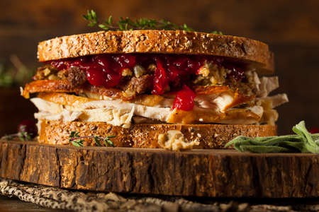 sandwich: Homemade Leftover Thanksgiving Sandwich with Turkey Cranberries and Stuffing Stock Photo