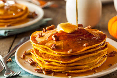 Homemade Pumpkin Pancakes with Butter Pecans and Maple Syrup Stockfoto
