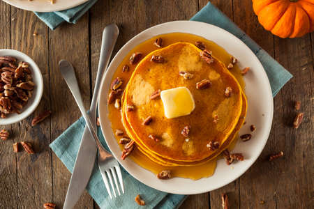 Homemade Pumpkin Pancakes with Butter Pecans and Maple Syrup Фото со стока