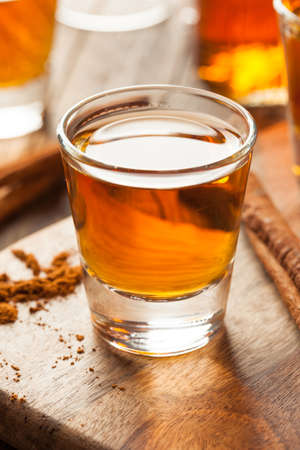 glass table: Cinnamon Whiskey Bourbon in a Shot Glass Ready to Drink Stock Photo