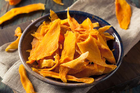 Raw Organic Dried Mangos in a Bowl Imagens